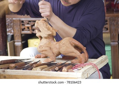 SUZHOU, CHINA - APRIL 27: An unidentified artist makes a statue from wood with a blade and a stick on April 27 2011 in Shuzhou, China. The place is considered the center of the oriental handicraft.