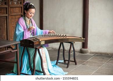 Suzhou, China - APRIL 9: A woman dressed in ancient chinese clothing playing the guzheng. April 9, 2011 in Suzhou City, Jiangsu Province, China.