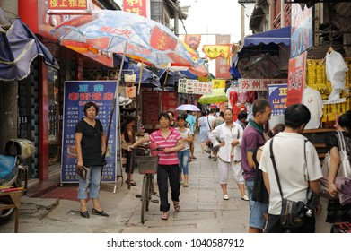 SUZHOU, CHINA - JULY 25, 2010: Pedestrian shopping area. Called Venice of the east, Suzhou is the most popular of water towns near Shanghai. Many visitors come to visit colorful streets near canals.
