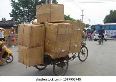 Suzhou, China - July 4 2009: An overloaded delivery bike with a stack of cardboard boxes carrying cargo