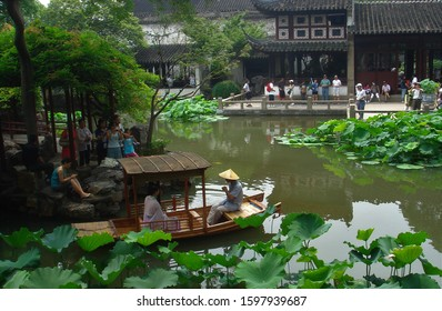 Suzhou, China - July 4 2009: A boat with a woman in traditional dress playing the pipa floats in a pond in the Lingering Garden