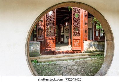 Suzhou, China - Nov 5, 2016: Master of Nets Garden (Wang Shi Yuan) – Moon gate doorway leading into a small residential courtyard designed in the classical Chinese architecture style.