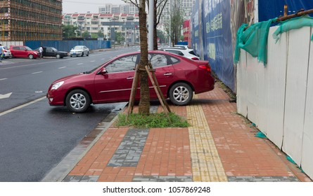 Suzhou, Jiangsu / China - July 21 2014: Cars in area undergoing development parked across sidewalk preventing or hindering pedestrian access.