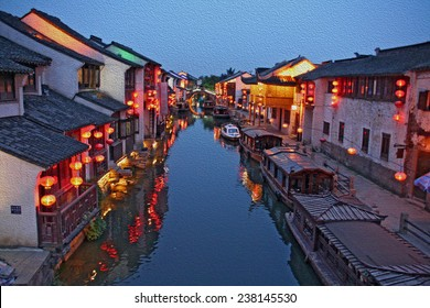 Suzhou old town in the evening, stylized and filtered to look like an oil painting  - a canal, boats, historic houses and chinese lanterns,  stylized and filtered to resemble an oil painting