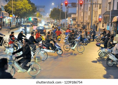 SUZHOU,CHINA-NOVEMBER 26,2017: Rush hour at a crossing with electric bicycles, electric mopeds and cars