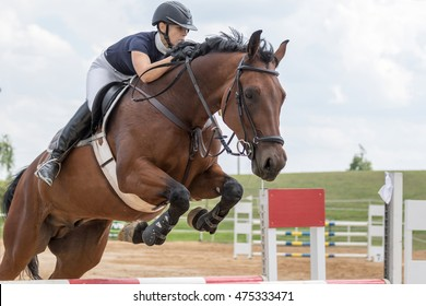 """SVEBOHOV, CZECH REPUBLIC - AUG 20: Closeup view of horsewoman jumping over obstacle at """"HobbyJumping Event  2016"""" on August 20, 2016  in Svebohov, Czech Republic."""