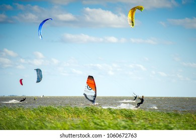 SVENCELE, LITHUANIA - AUG 13, 2017: People kiteboarding and windsurfing in Curonian Lagoon, Svencele, Dreverna, Lithuania. The kite boarding and windsurfing centre in Svencele.