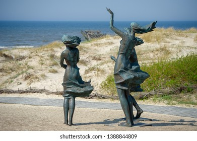 """Sventoji, LITHUANIA - APRIL 28, 2019: The sculpture """"Fisherman's daughters"""" in the dunes, near the gates of Sventoji port. Three girls are looking at the sea and waiting for their father to come back."""