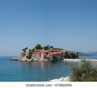 Sveti Stefan, Budva, Montenegro. Sunbathing and swimming people on Sveti Stefan pebble beach in front of Sveti Stefan island pictured on sunny summer day.