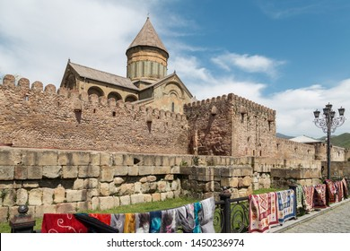 Svetitskhoveli cathedral of 12 Apostles in Mtskheta, ancient capital of Georgia, with traditional carpets on foreground