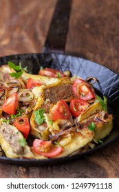 swabian maultasche with onions in an iron pan