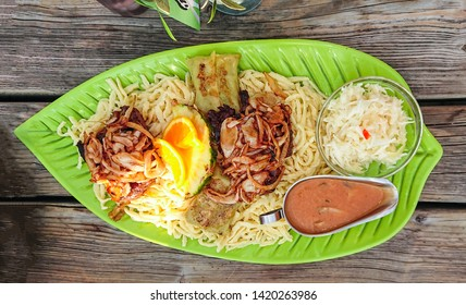 Swabian spaetzle, maultaschen with fried onion rings and gray sauce, top view