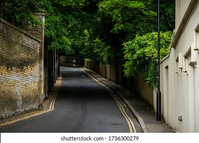 Swain's Lane, Highgate, London. A lone cyclist rides up the hill under overhanging trees in a moody daytime lighting