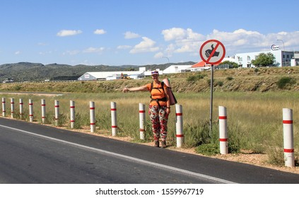 """Swakopmund, Namibia - May 15, 2015: Young white tourist girl backpacker hitchhiking and stops the car under the sign """"hitchhiking is prohibited."""""""