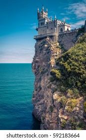 Swallow's Nest castle on the rock at the Black Sea in summer, Crimea, Russia. It is a symbol and landmark of Crimea. Amazing vertical view of Swallow's Nest castle over the precipice.
