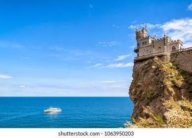 Swallow's Nest castle on a tall rock over Black Sea, Crimea, Russia. Postcard of Crimea. Swallow's Nest is a landmark and symbol of Crimea. Beautiful scenic panorama of the Crimea coast in summer.