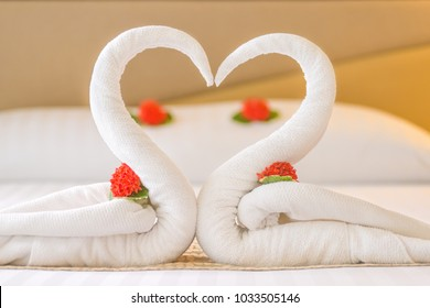 Swan couple put on honeymoon bed look like heart shape with flower petals for honeymoon lover in the room decoration make romantic feeling.
