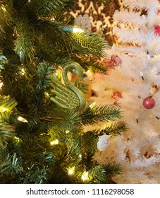 A swan ornamnent sparkling with green and gold glitter hangs from a branch of a Christmas tree in modern Christmas tree garden.