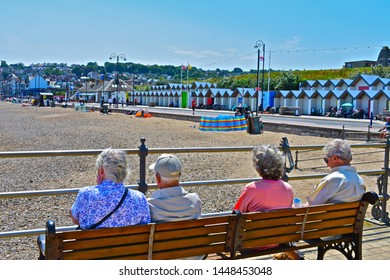 Swanage, Dorset / England - 6/26/2019: two older couples relaxing and enjoying sitting in the summer sunshine on the banjo pier overlooking the beach and shoreline.Rows of beach huts beyond promenade.