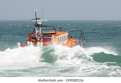 SWANAGE, DORSET – JULY 21 2013: RNLI Mersey class lifeboat Robert Charles Brown launches into choppy seas on 21 July 2013 to assist a vessel in distress. This lifeboat was based in Swanage, Dorset.
