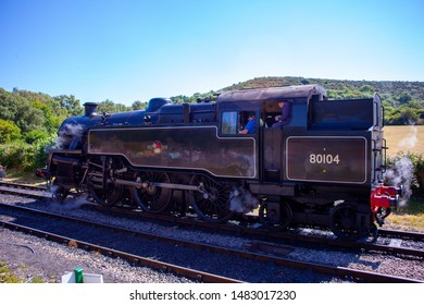 Swanage, Dorset, United Kingdom - July 15, 2019: Steam Train at Swanage Railway at the Norden station. BR Standard Class - BR 2-6-4T Class 4MT No. 80104. Vintage steam train stopped at station.