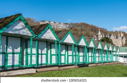Swansea, South Wales UK 02/02/2019 Beach huts in Langland Bay, The Mumbles, Gower, South Wales, with the old hotel nestling in the trees behind. Very popular beach with families and tourists.
