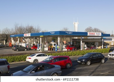 Swansea, UK: December 28, 2016: Cars queue to leave a shopping mall. A Tesco petrol station is behind with customers refueling their vehicles.
