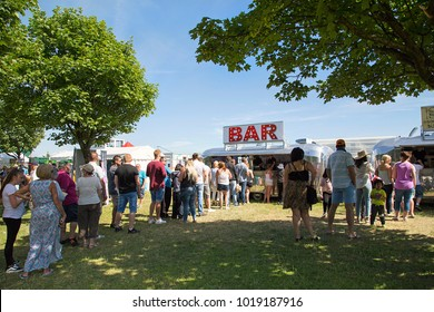 Swansea, UK: July 07, 2017: People wait in line to be served a drink at Swansea Air Show. The annual free event has concession stands selling food and refreshments.