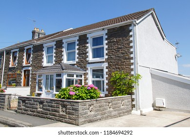 Swansea, UK: July 07, 2018: Street view of typical double fronted terraced house in a Welsh village. Summertime with flowers in the garden and blue skies.
