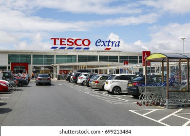 Swansea, UK: July 09, 2017: Front view of a Tesco Extra Superstore in Wales. Tesco PLC is a British multinational grocery and general merchandise. Shoppers are entering or leaving the shop.