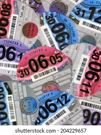 SWANSEA, UK - JULY 11, 2014: Photo of a collection of UK car tax discs showing different years.