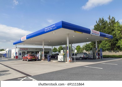 Swansea, UK: June 01, 2016: Customers are using the dispensers to fill their cars with petrol at a Tesco Petrol Station.