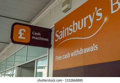 SWANSEA, WALES - JULY 2018: Exterior of a Sainsbury's supermarket in Swansea with a sign for a cash point machine