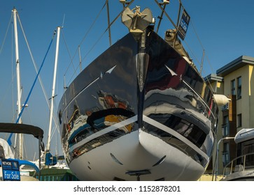 SWANSEA, WALES - JULY 2018: Head on view of the bow of a yacht for sale in Swansea marina. The hull is painted in gloss black which is reflecting its surroundings.