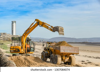 SWANSEA, WALES - OCTOBER 2018: Excavator loading a truck with sand on the beach in Swansea after winds had blown it to the seafront.