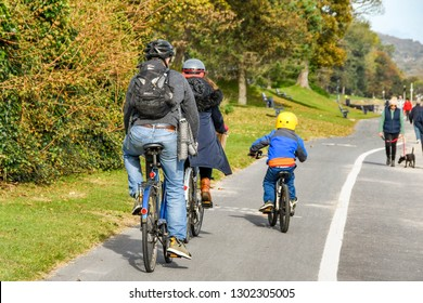 SWANSEA, WALES - OCTOBER 2018: Family cycling along the coastal path from Mumbles to Swansea.