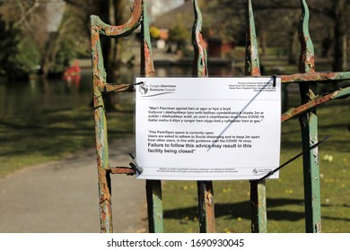Swansea, Wales, UK - March 31, 2020: Coronavirus Covid 19 social distancing sign on a park gate