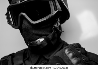SWAT in black uniform, face mask and bulletproof vest.Special forces.Tactical helmet vest goggles.Spec ops Riot police officer Defense and protection of law enforcement officers.Black and white photo