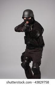 SWAT police officer aiming a shotgun.
