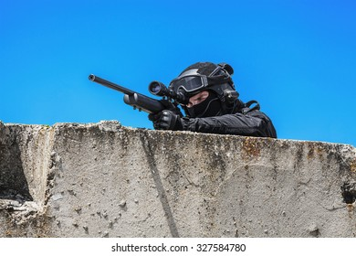 Swat police operator with sniper rifle in black uniforms aiming criminals terrorists waiting in stakeout behind concrete block. Sunny day, low angle