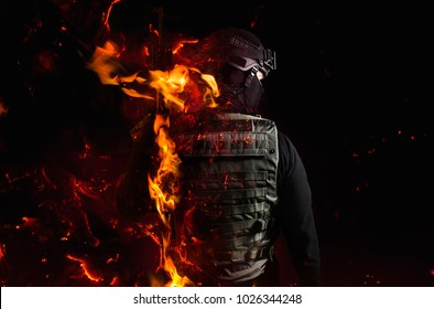 Swat soldier with fire effects. Photo of a swat soldier`s back with flame effect on black background.