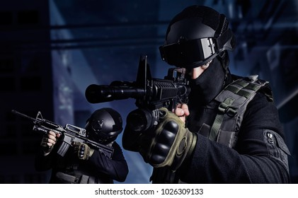 Swat soldiers on night streets. Photo of a swat soldiers posing with automatic rifles on a night city background.