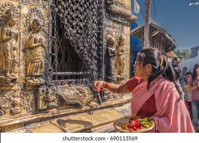 Swayambhunath, best loved Buddhist temple (also called Monkey Temple), Kathmandu, Nepal-October 17, 2008: Women passing by one of Buddha's spiritual icons, touching it or lighting candles
