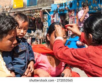 SWAYAMBHUNATH, KATHMANDU, NEPAL-OCTOBER 17, 2008: A woman puts Tika on young women's forehead to bless them with abundance during Dashain festival. Tika is a mixture of rice, yogurt and vermilion.