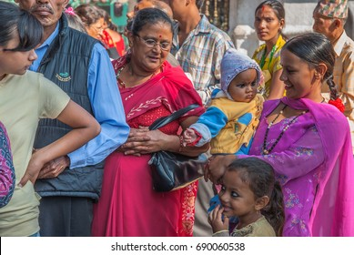 Swayambhunath, loved Buddhist Temple (Monkey Temple), Kathmandu, Nepal -October 17, 2008: Families, men, women, children & babies standing in line to make offerings to Buddha at a religious festival