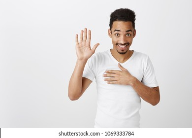 Swear to say truth. Studio shot of sincere happy african-american male with afro haircut, raising palm and holding hand on chest, promising to me honest, standing over gray background