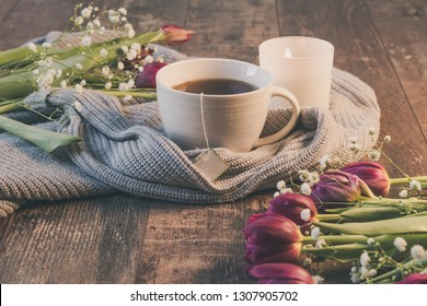 Sweater with cup of tea and tulips