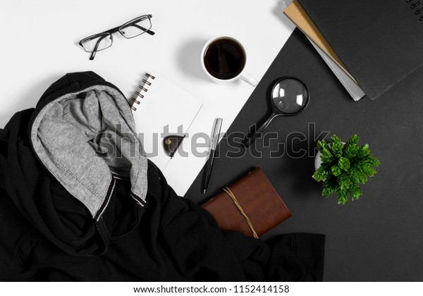 Sweater, notebook, coffee cup, and personal items on black and white background.