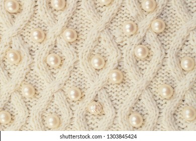 Sweater or scarf a great texture knitting. Pearl finish. Knitted Jersey background with embossed pattern. Braids in knitting. Hand-knitted or machine-knitted wool with a pattern. The Fabric Background