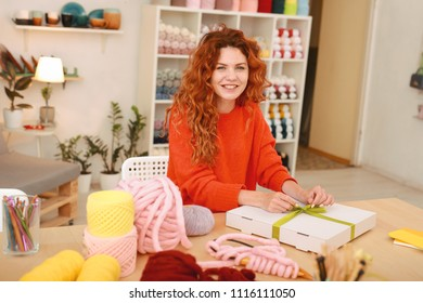 Sweaters for clients. Smiling broadly professional needlewoman feeling very busy while packing sweaters for her clients